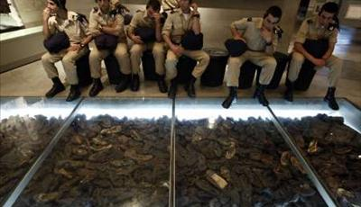 Young Israeli soldiers contemplating a collection of shoes from victims sent to the furnaces.