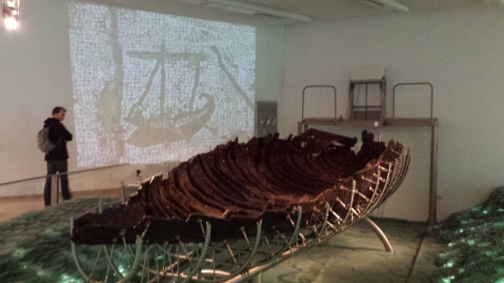 The Jesus boat - notice the image projected on the wall behind it from an old mosaic of exactly this type of boat